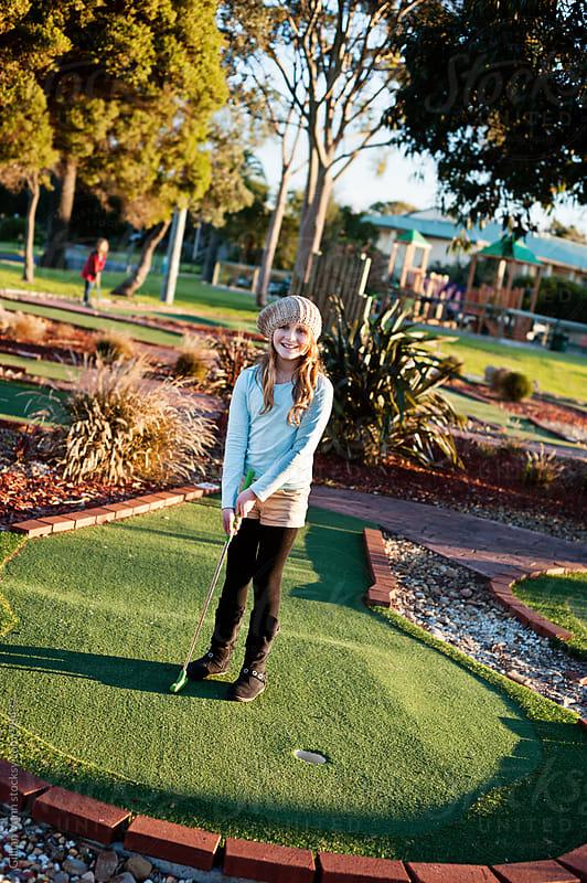 girl playing mini golf by Gillian Vann for Stocksy United