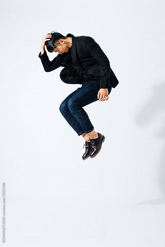Asian man wearing black suit jumping over white background.  by BONNINSTUDIO for Stocksy United