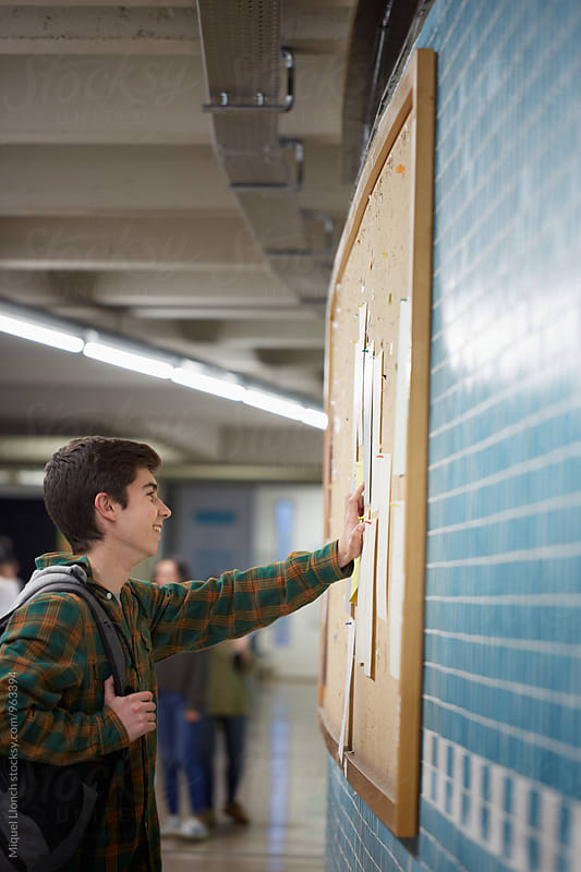 Young student reading good news on a board of the university by Miquel Llonch for Stocksy United