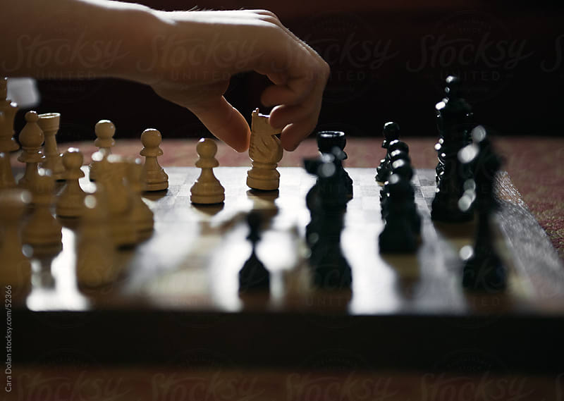 Child's hand reaches in to make a move in chess by Cara Dolan for Stocksy United