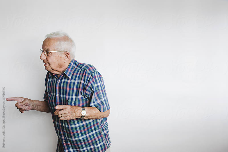 Funny senior man telling stories on white background by Rob and Julia Campbell for Stocksy United