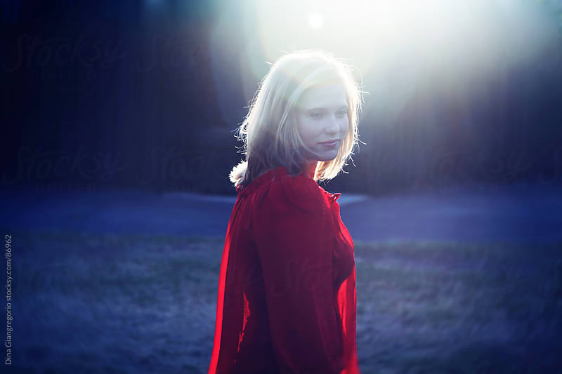 Pretty girl in red with sun flare by Dina Giangregorio for Stocksy United