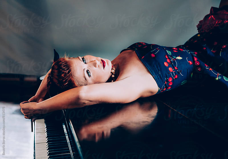 Woman in cherry dress lying on the piano by Beatrix Boros for Stocksy United