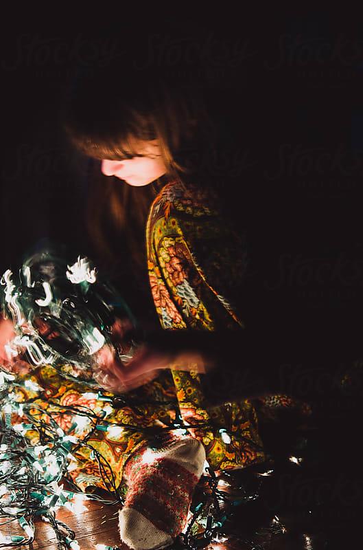 girl sitting on floor winding lights on a holder by Deirdre Malfatto for Stocksy United