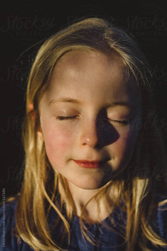 A little girl enjoying sunshine with her eyes closed. by Helen Rushbrook for Stocksy United