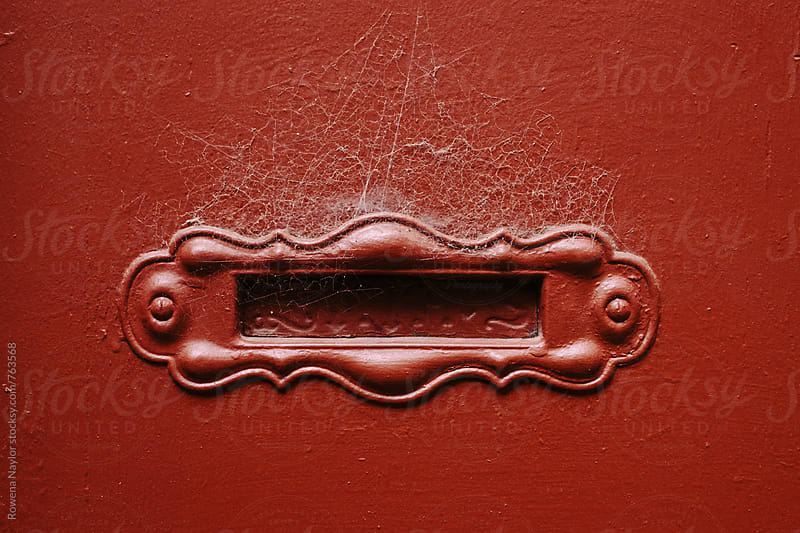 Red letterbox with cobwebs by Rowena Naylor for Stocksy United