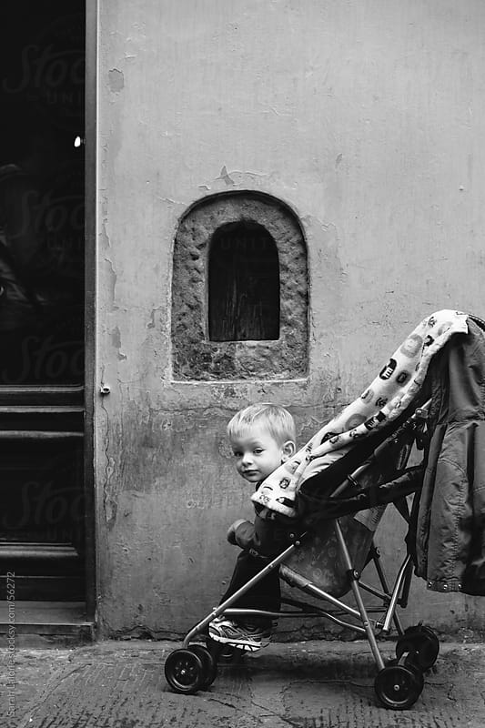 A little boy in a stroller on a sidewalk in front of a store in Florence by Sarah Lalone for Stocksy United