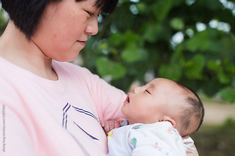 Young mother holding her baby boy by zheng long for Stocksy United