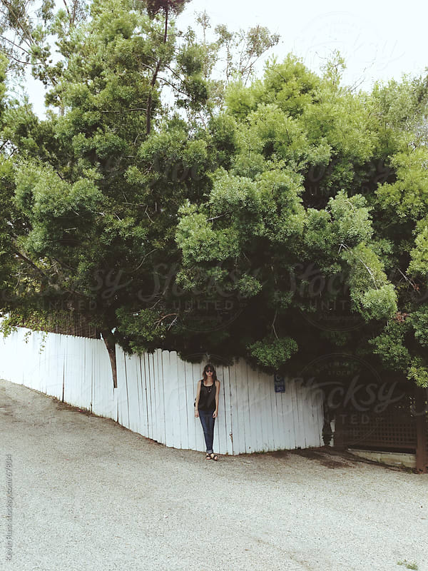 Woman Standing Under Tree Against Fence by Kevin Russ for Stocksy United