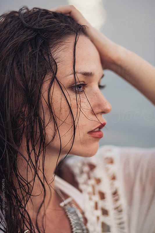 Beautiful young woman on the beach by Maja Topcagic for Stocksy United