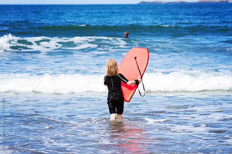 A little girl walking into the sea carrying her surf board by Helen Rushbrook for Stocksy United