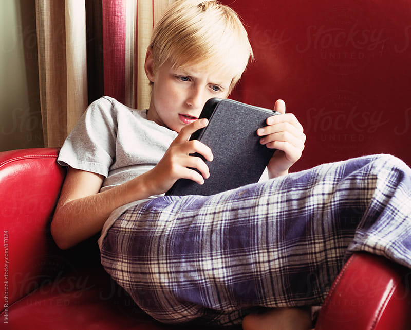 A young boy reading an E-Book on an E-reader by Helen Rushbrook for Stocksy United