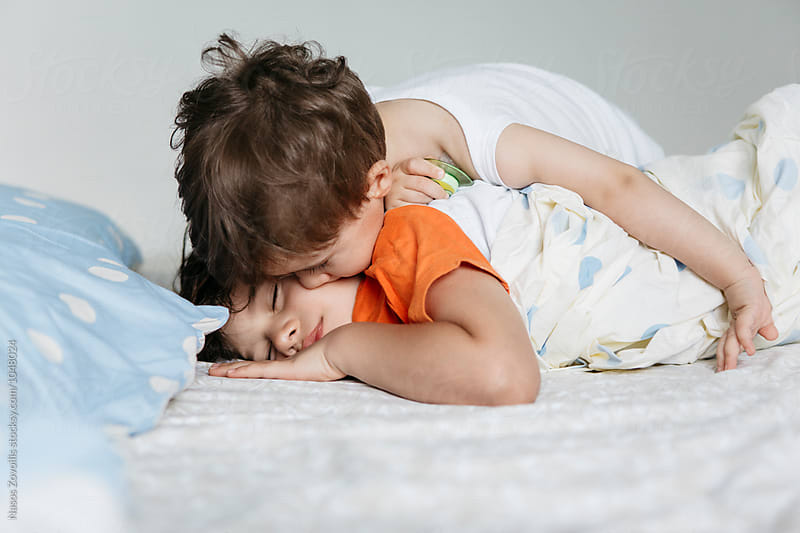 1 year old boy kissing his brother by Nasos Zovoilis for Stocksy United