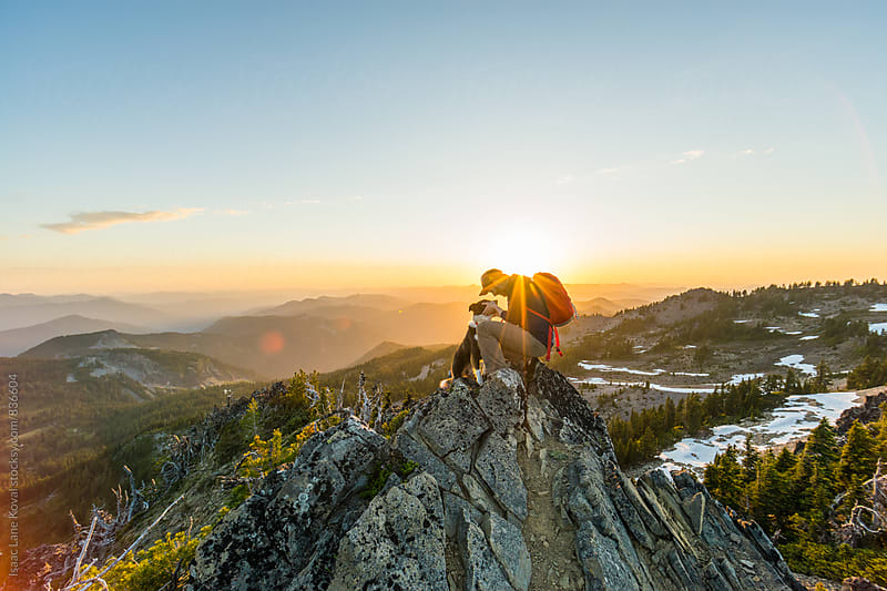 Man and his dog ontop of mountain at sunset by Isaac Lane Koval for Stocksy United
