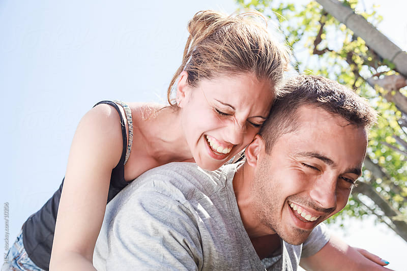 Young Smiling Couple are Playing Outdoor by HEX. for Stocksy United