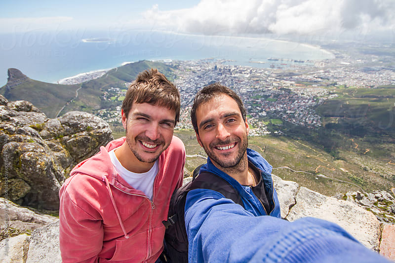 Two young happy men friends taking a selfie, on top of Table Mountain with Cape Town city on the background, South Africa by Alejandro Moreno de Carlos for Stocksy United