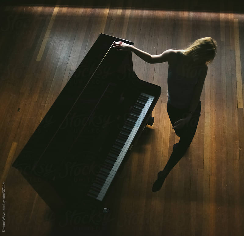 Dancer performing in front of a piano by Simone Becchetti for Stocksy United