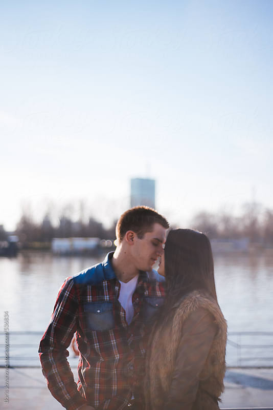 Young couple kissing on a dock by Boris Jovanovic for Stocksy United