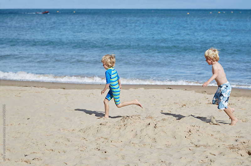 Children having fun playing on the beach together by sally anscombe for Stocksy United
