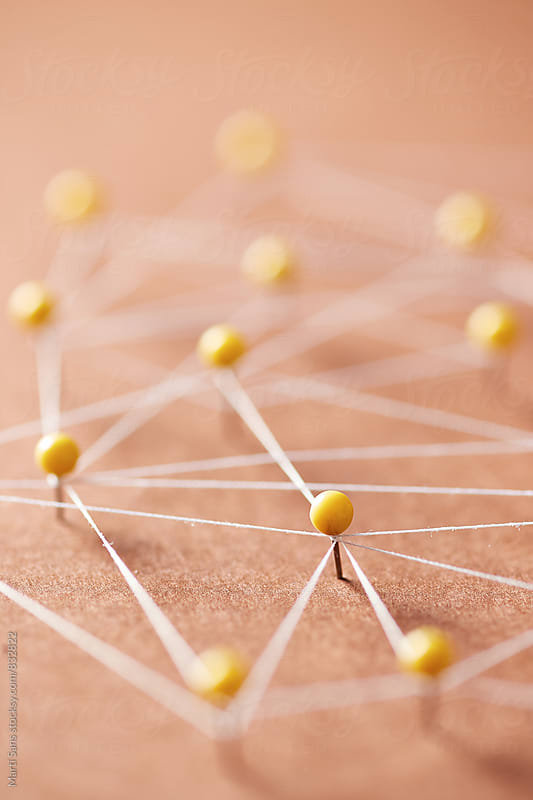 Close-up of yellow pins on beige background creating a network by Martí Sans for Stocksy United