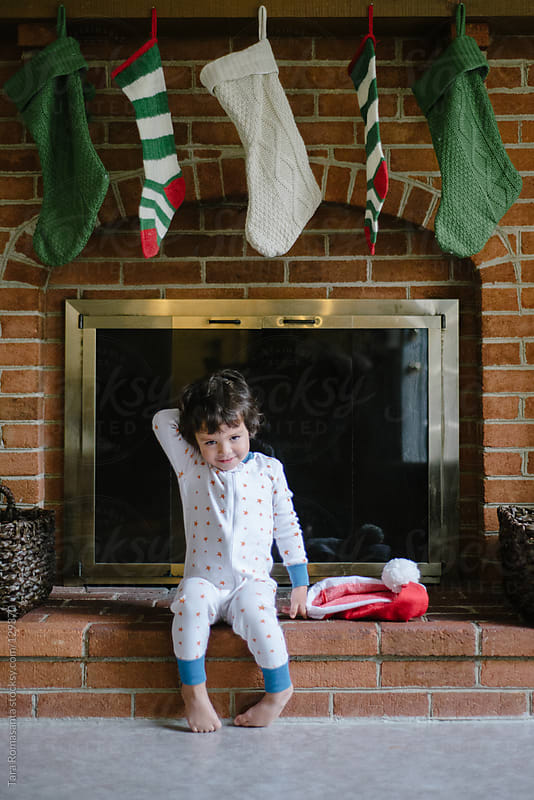 boy in pajamas sits in front of fireplace with stockings by Tara Romasanta for Stocksy United