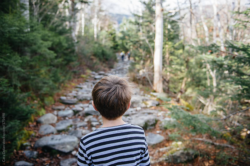 Boy looks forward towards a mountain hiking trail by Cara Dolan for Stocksy United