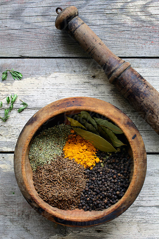 Тhyme, caraway, pepper, turmeric, oregano, bay leaf in mortar with pestle by Pixel Stories for Stocksy United