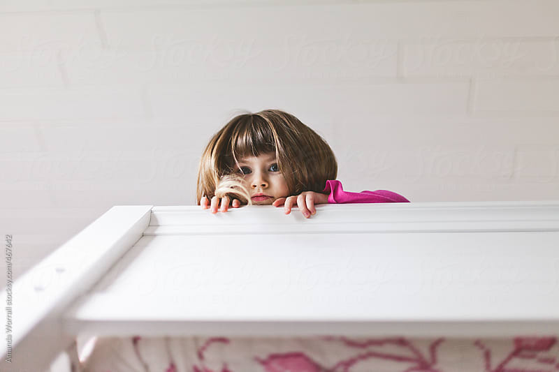 Little girl peeking over edge of bunk bed by Amanda Worrall for Stocksy United
