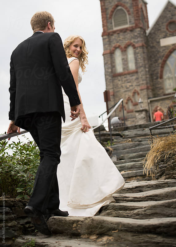 Beautiful natural bride with groom on steps of old church by Brian McEntire for Stocksy United