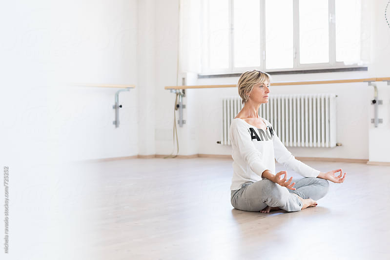 Mature woman doing asana for meditation  by michela ravasio for Stocksy United