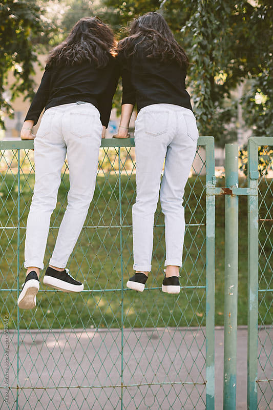 teen girls climbing over the fence . by Alexey Kuzma for Stocksy United