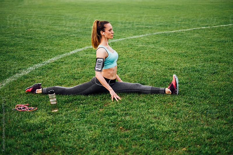 Attractive Brunette Woman Stretching on the Grass by Katarina Radovic for Stocksy United