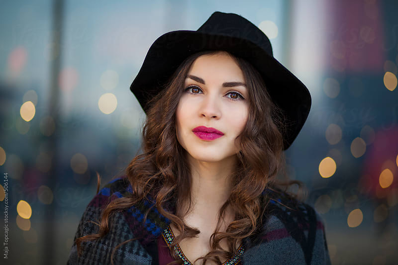 Young beautiful woman with black curly hair and red lipstick walking in the city by Maja Topcagic for Stocksy United
