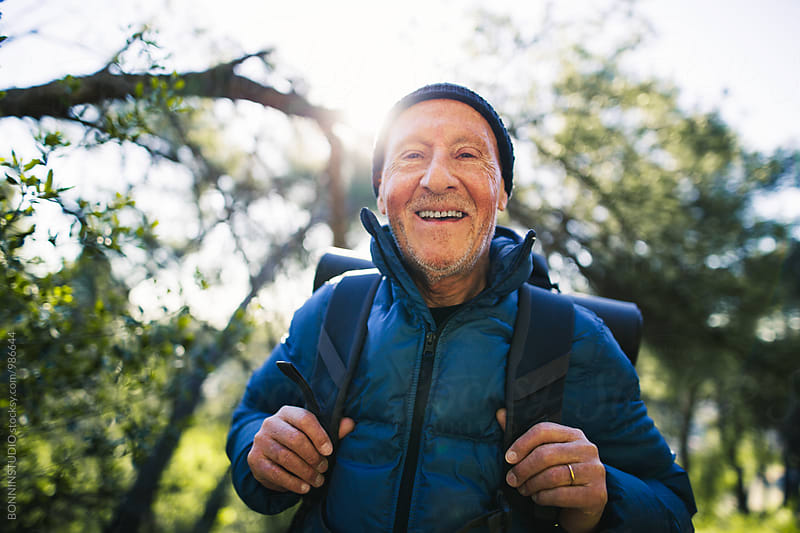 Portrait of a hiker senior man smiling in the woods.  by BONNINSTUDIO for Stocksy United