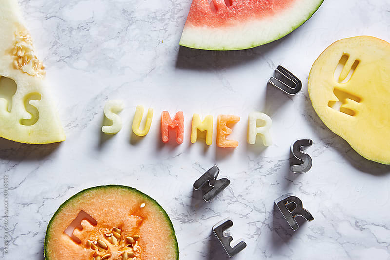 Summer fruit letters on table with slices of fresh exotic fruit by Martí Sans for Stocksy United