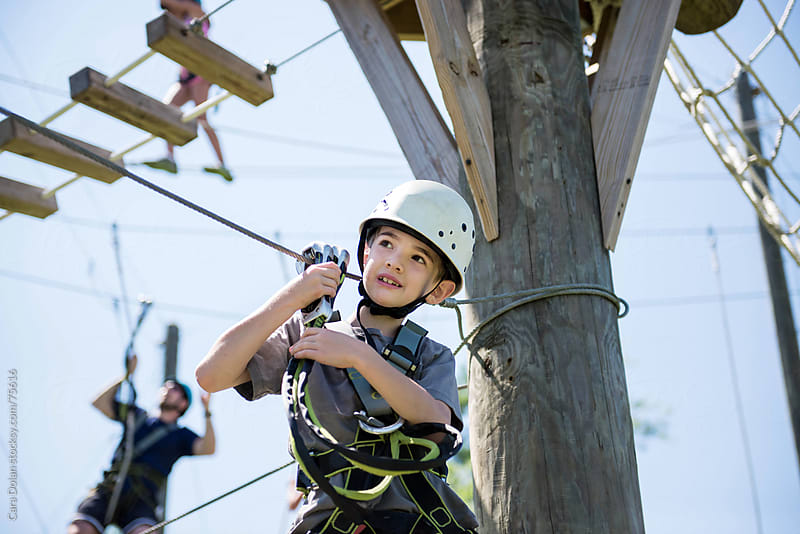 Boy with harness and helmet climbs on a ropes course by Cara Dolan for Stocksy United