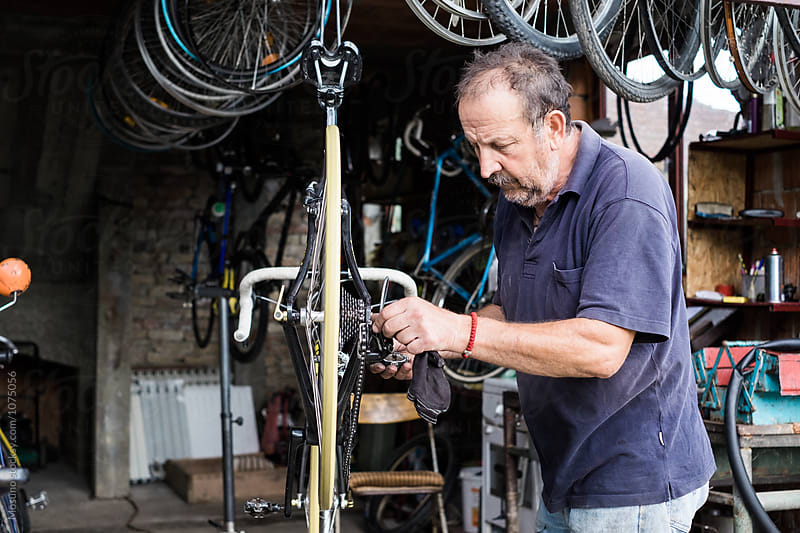 Senior Man Repairing a Bike  by Mosuno for Stocksy United