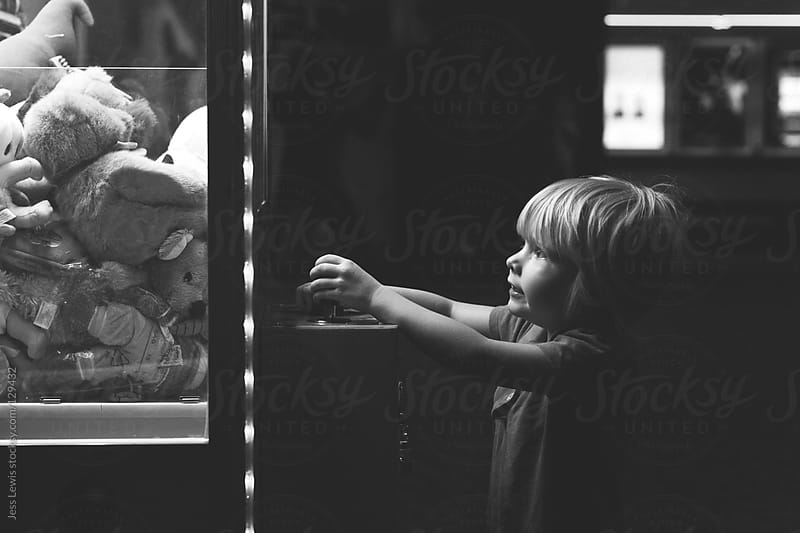 young girl playing arcade game by Jess Lewis for Stocksy United