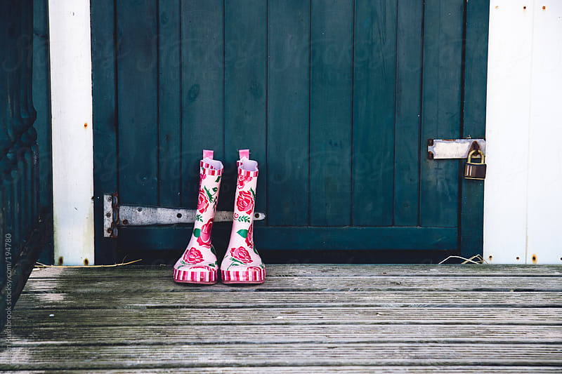 Floral wellies in front of a beach hut door by Helen Rushbrook for Stocksy United