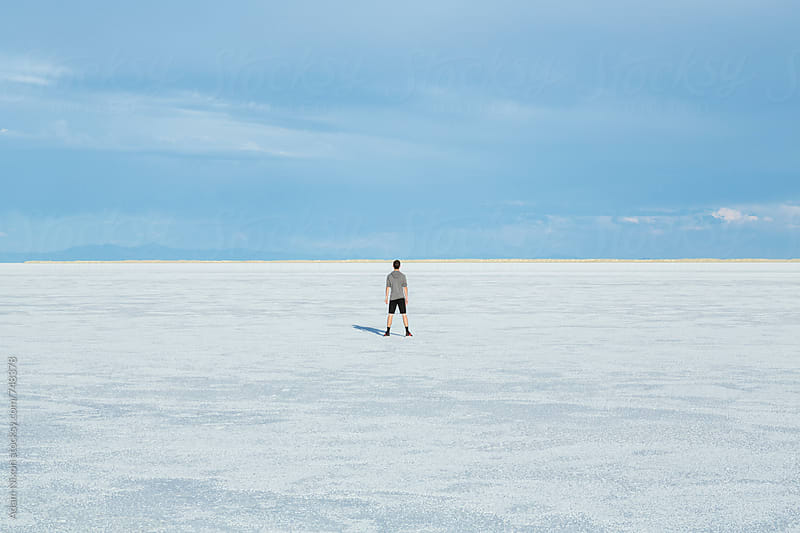 Teenage boy standing on the vast salt flats of Utah by Adam Nixon for Stocksy United