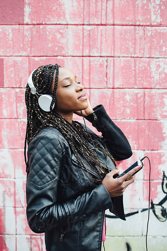 Young woman relaxing with headphones outdoors by michela ravasio for Stocksy United