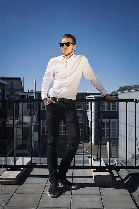 Hip young man with sunglasses is standing on a balcony by Koen Meershoek for Stocksy United