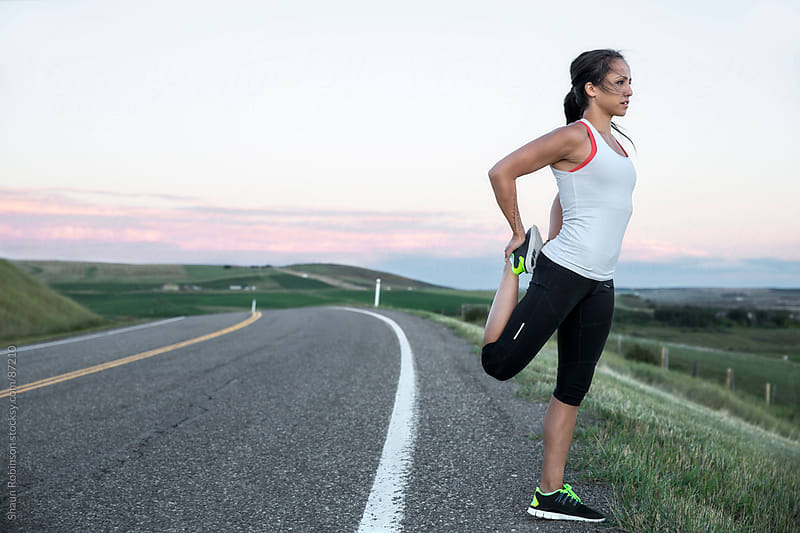 a young athletic woman stretching on the side of a paved road by Shaun Robinson for Stocksy United