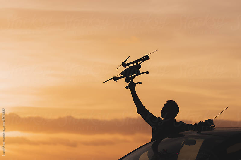 Man using a drone at sunset by Luca Pierro for Stocksy United
