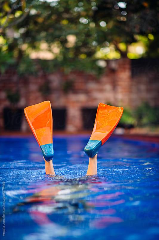 Boy wearing fins in a pool by Angela Lumsden for Stocksy United