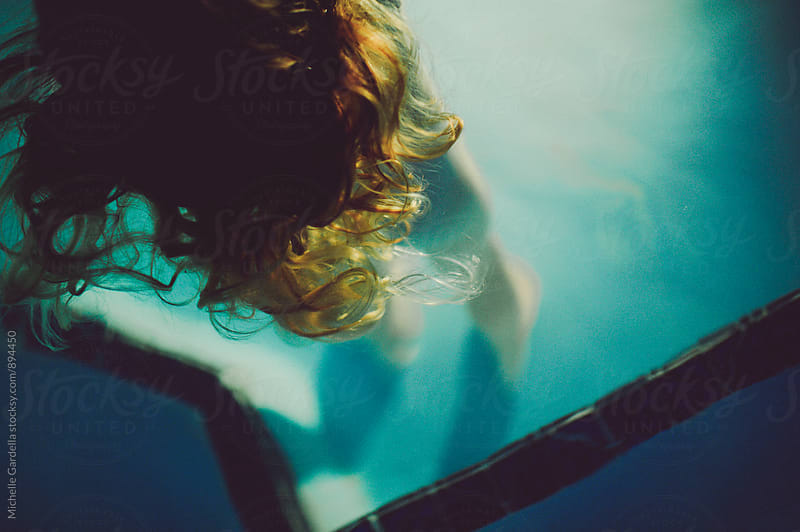 Hair in pool   by Michelle Gardella for Stocksy United