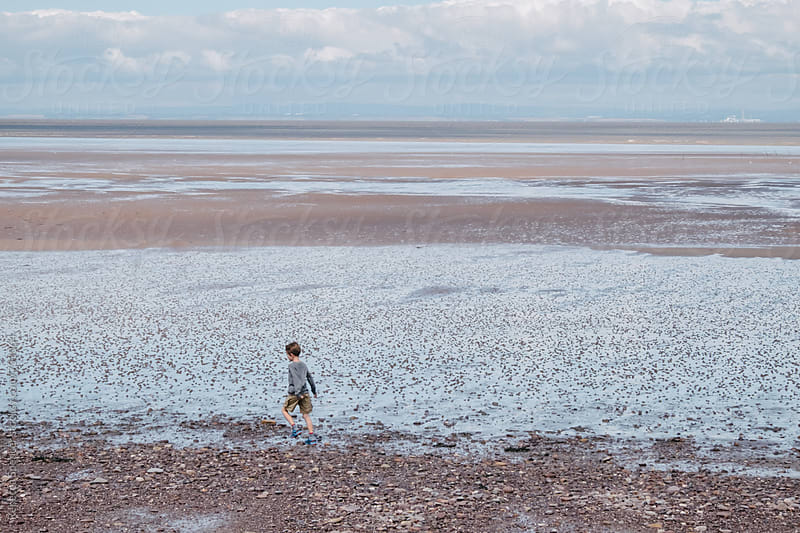 Child runs alnong the mud flats of north Somerset by Rebecca Spencer for Stocksy United