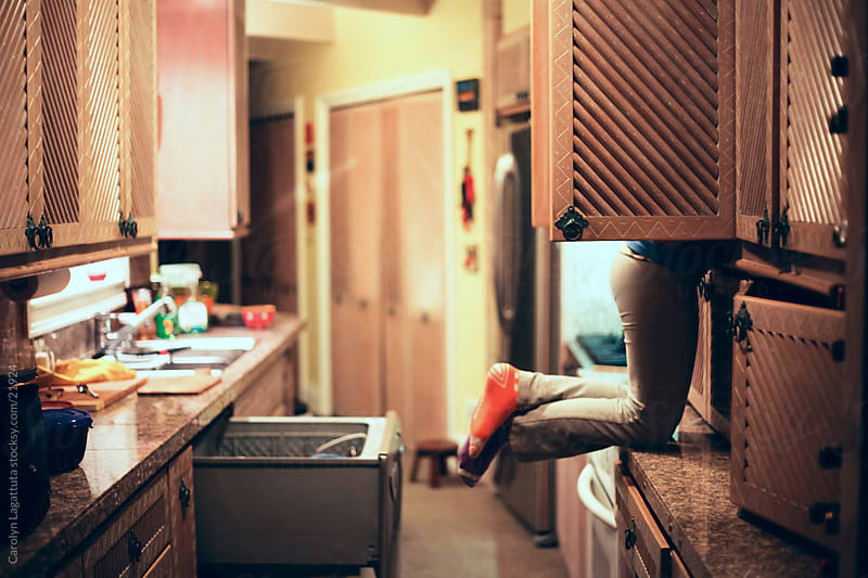 Girl on the counter with her face in the cabinet, looking for something to eat. by Carolyn Lagattuta for Stocksy United