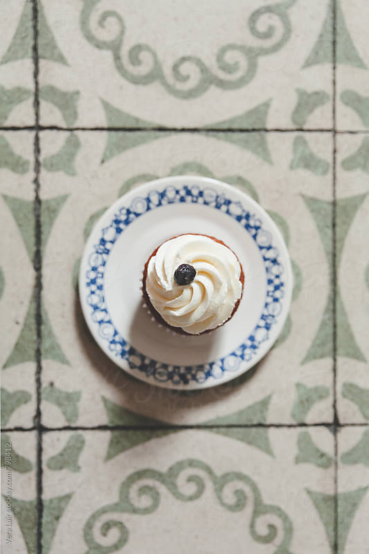 A plate with a cup cake placed on old tiles by Vera Lair for Stocksy United