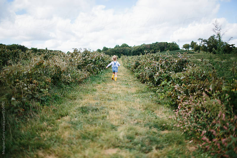 little girl running through a field in boots and overalls by Meaghan Curry for Stocksy United